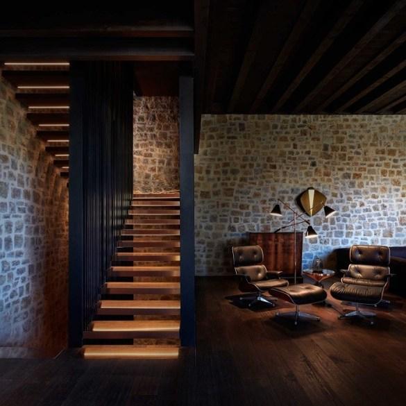 zona de lectura con dos sillones y una lámpara al lado de la escalera