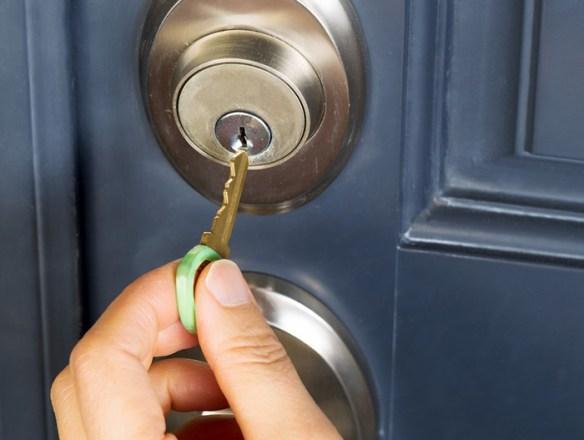 persona abriendo puerta con llave