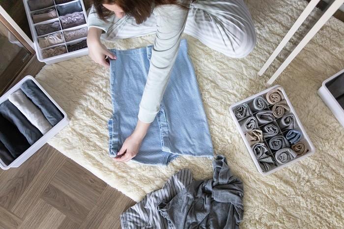 Mujer en su hogar ordenando y colocando la ropa de sus cajones