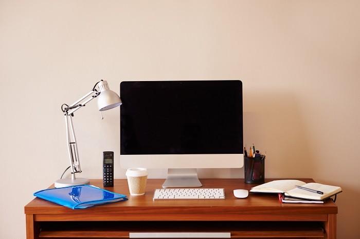 zona de teletrabajo con escritorio con portátil, flexo, libreta, teléfono y demás objetos