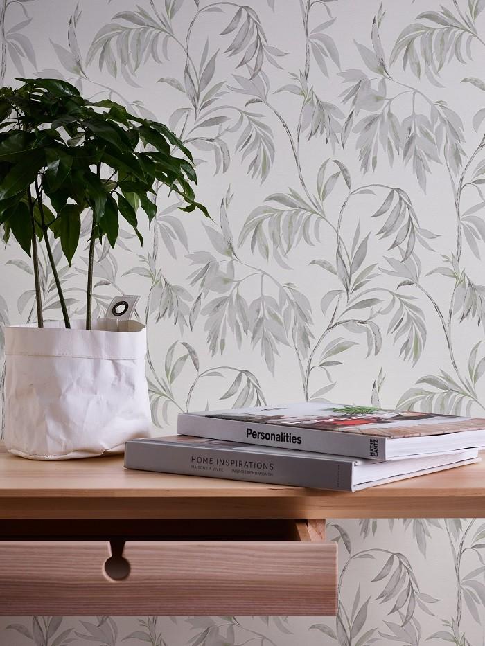 mesa con libros y una planta y de fondo una pared con papel pintado de motivos florales