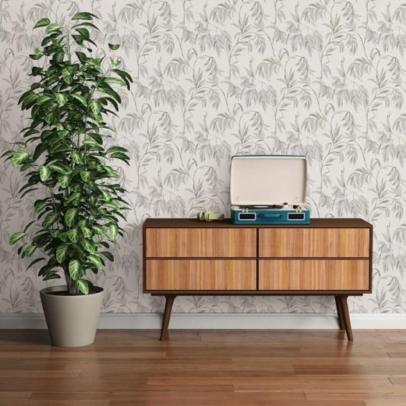 zona de mueble con planta y pared con papel pintado floreado