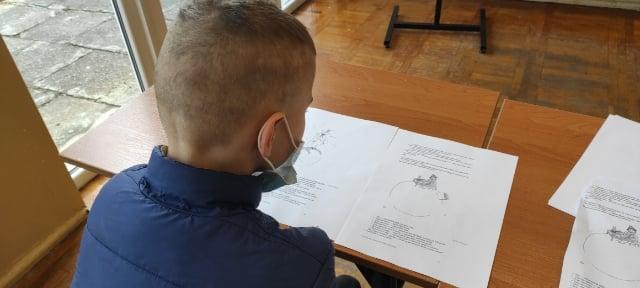 Na zdjęciu chłopiec odrabia zadanie domowe