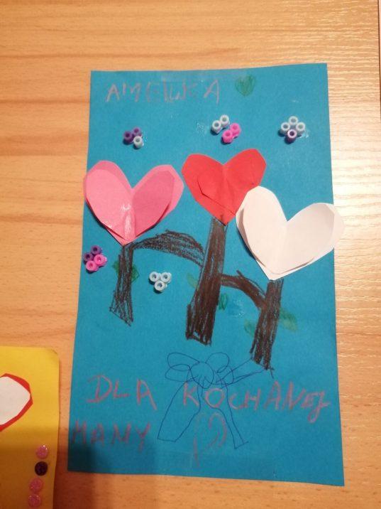 Zdjęcie przedstawia wyróżniony rysunek. Są nanim  serca wykonane zpapieru ozdobione przyklejonymi koralikami