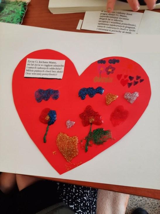 Zdjęcie przedstawia wyróżniony rysunek, naktórymwidać Serce ozdobione brokatem, którymznajdują się życzenia dla mamy