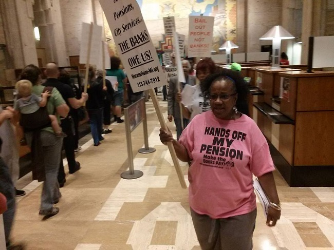 Demonstrators march inside the Bank of American branch in the Guardian Building during Freedom Friday 6, June 13, 2014.