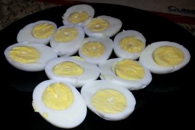 Slice the hard boiled eggs in half, then remove the egg yolks.