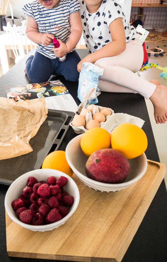Pavlova-backen-mit-Kindern-Mango-Orangen-Himbeeren-auf-Brett-zwei-Kinder-sitzend