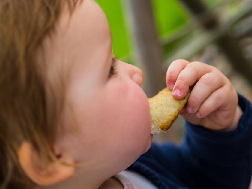 Weidentipi mit Kindern bauen_Mädchen isst Stockbrot