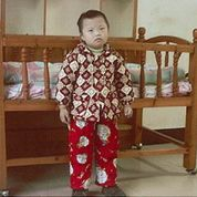 Macy at her orphanage standing next to her bed.