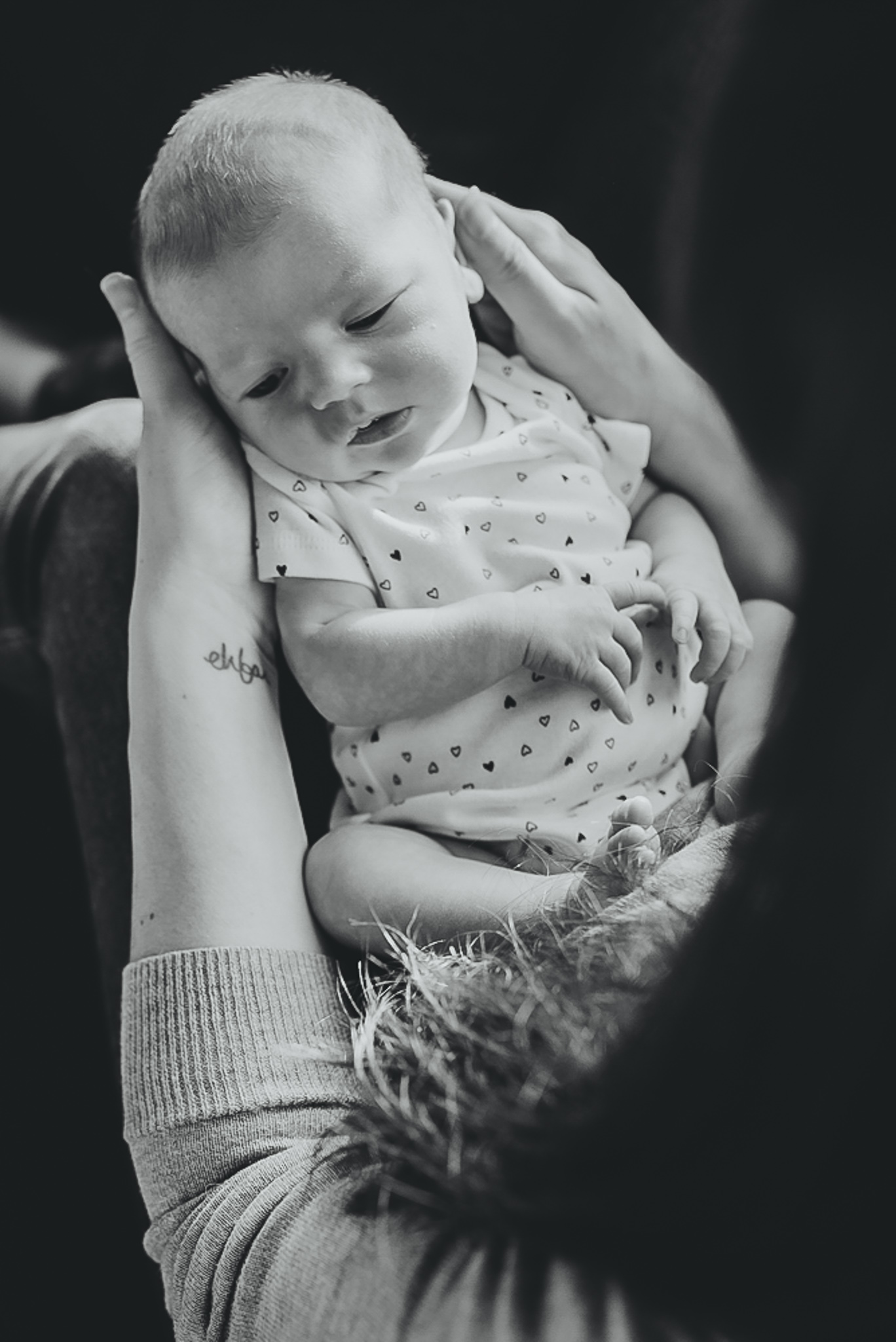 Mom holding baby in lap during newborn photoshoot