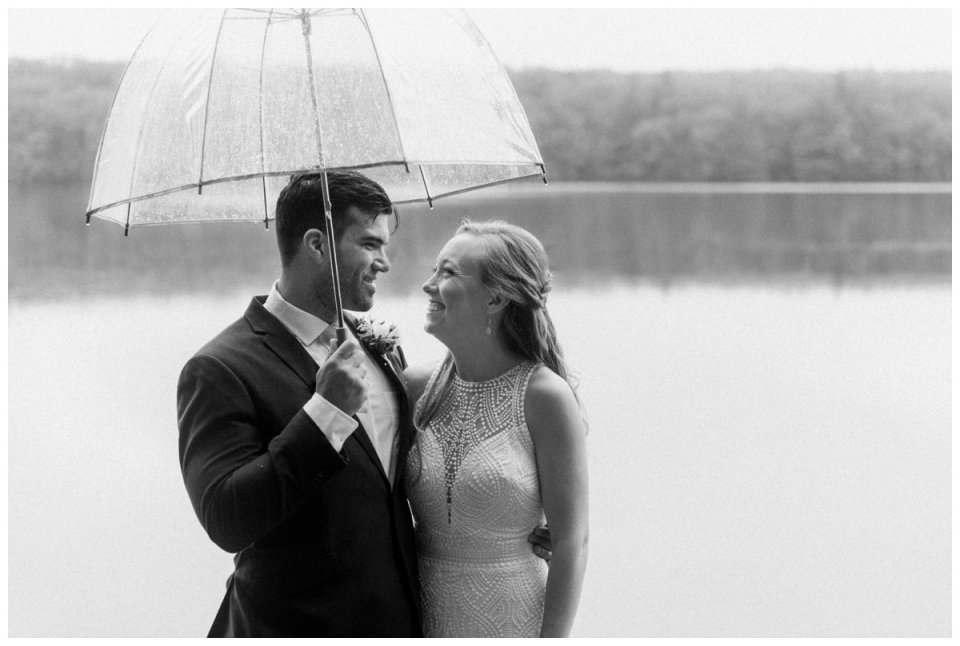 loving photo of bride and groom happy and smiling under umbrella