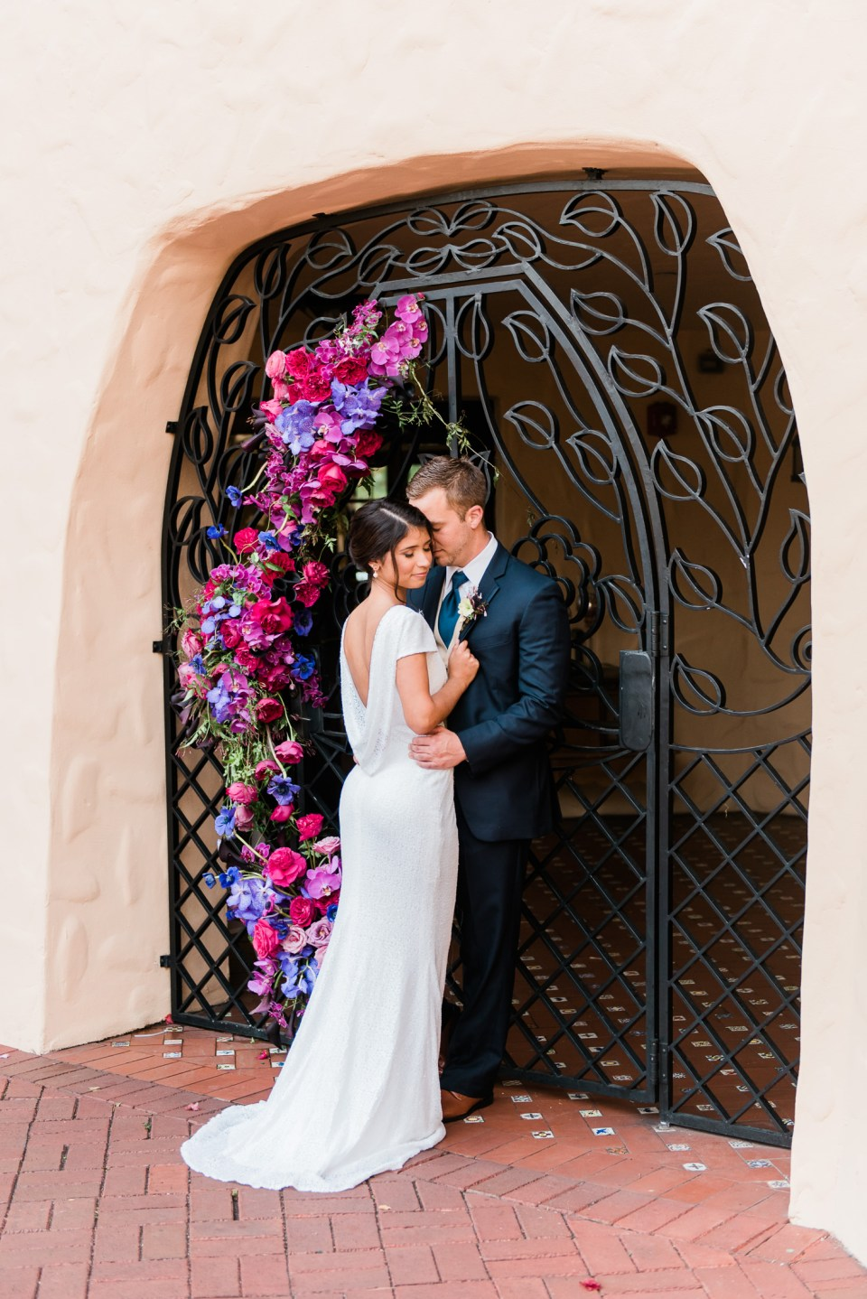 A wedding portrait of a couple under an elaborate floral installation at Curtiss Mansion in Miami Springs, florida
