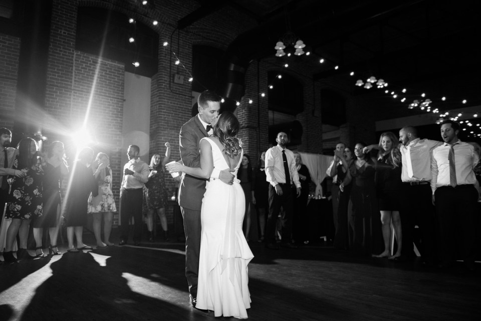 bride and groom dance surrounded by friends at Charles River Museum of Industry and Innovation wedding