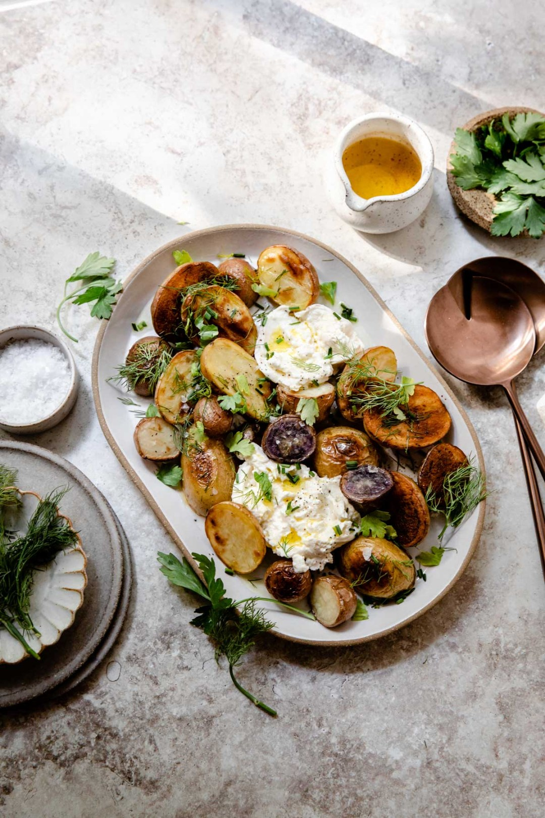 Roasted potatoes with bunches of fresh herbs and creamy burrata make the perfect gluten-free side dish for any weeknight dinner or weekend gathering.