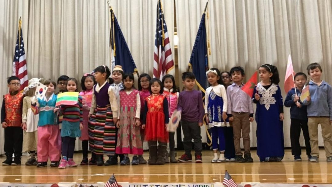 A class of students standing on a school stage while wearing traditional cultural costumes in honor of RFA Week