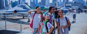 Four girls posing in front of camera on deck of the USS Intrepid