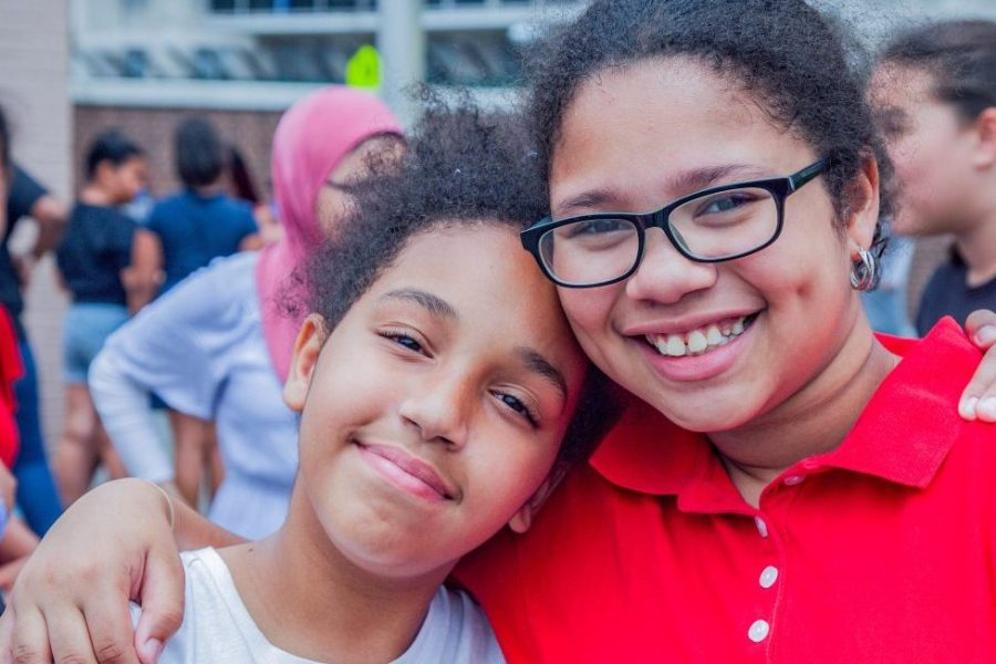 Two NYC students embracing one another while smiling for a photo