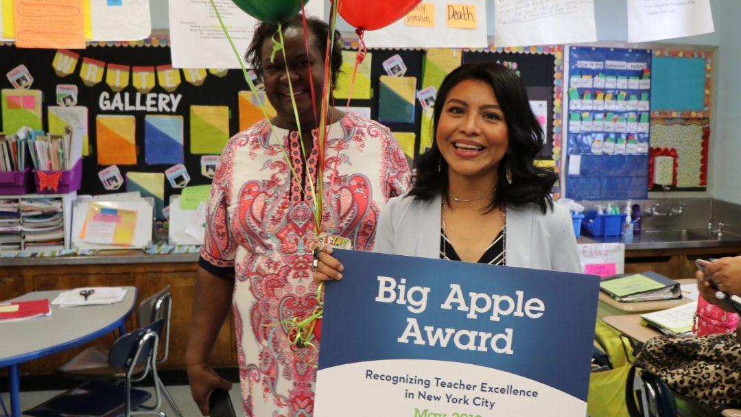 "Yadira Hans (center) holding a ""Big Apple Award"" sign"