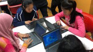 Four girls designing CGI monsters on their laptops