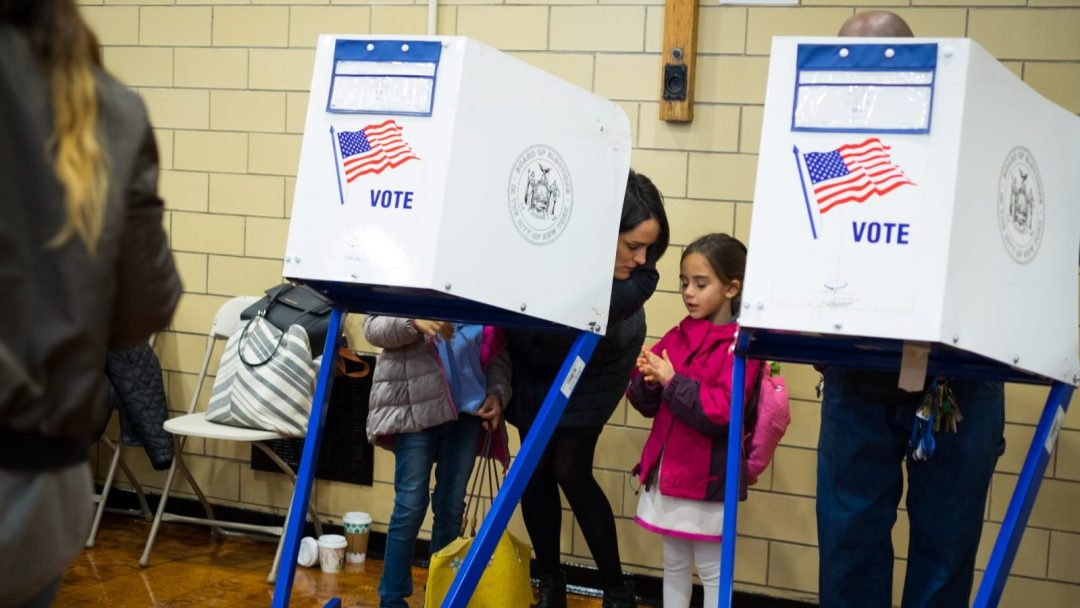 A mother and her daughter behind a voting booth on Election Day