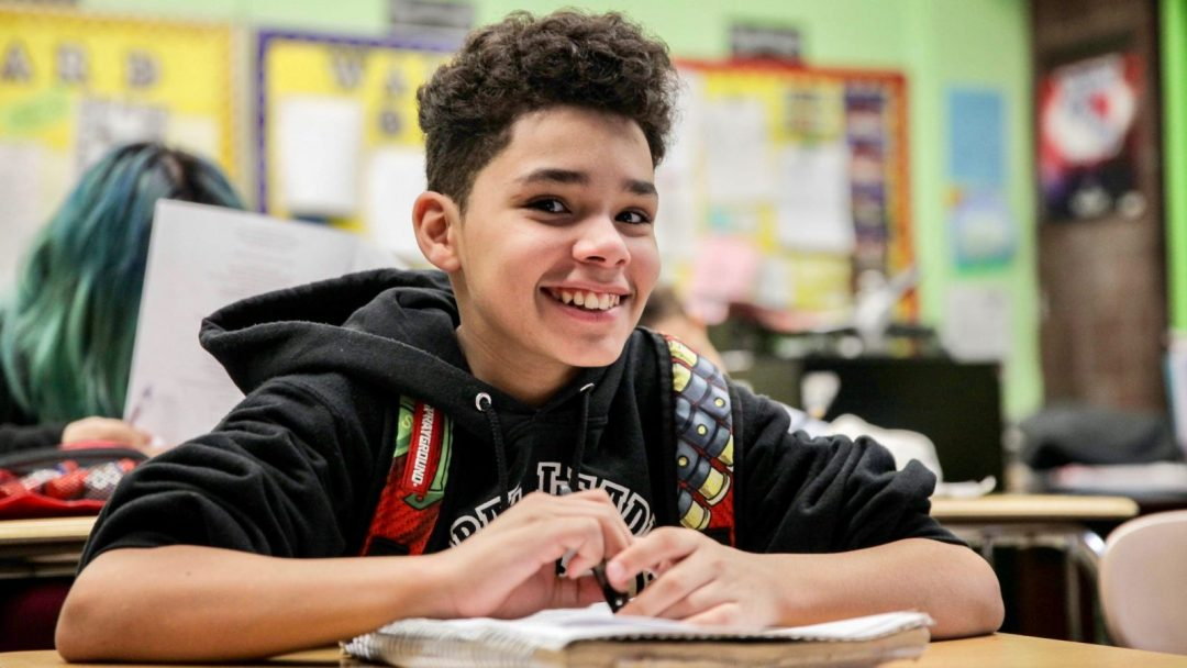 Boy student smiling at viewer while sitting at a desk inside a classroom.