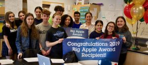 Paraskevi Langis (right of center, yellow striped shirt) poses with her class following her receipt of her 2019 Big Apple Award