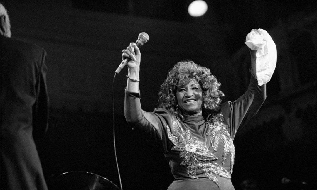 Celia Cruz, holding both hands in the air, while performing onstage