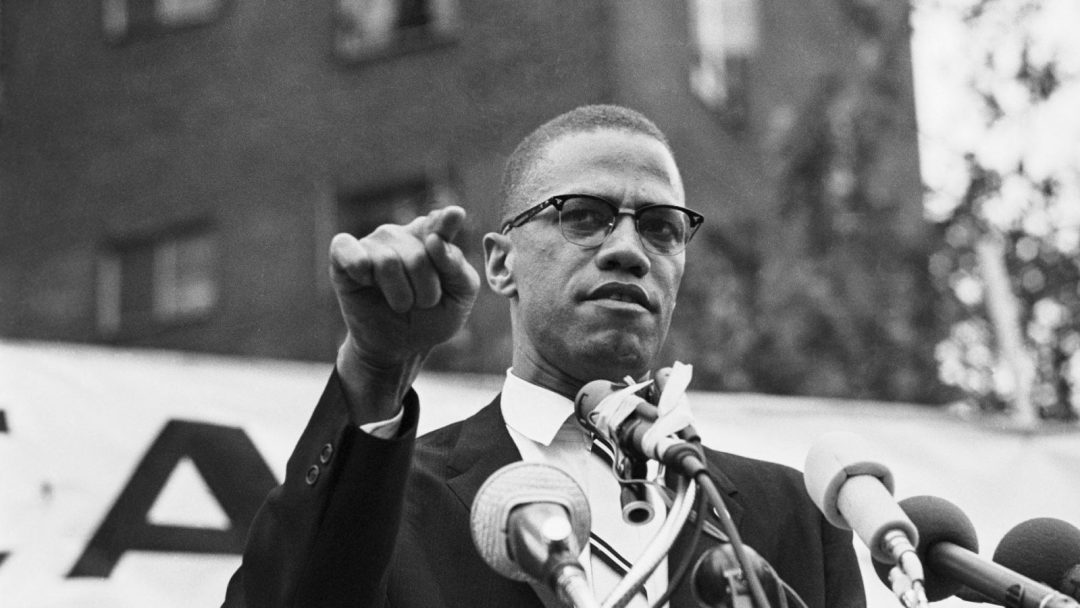 Malcolm X in mid-speech at a podium