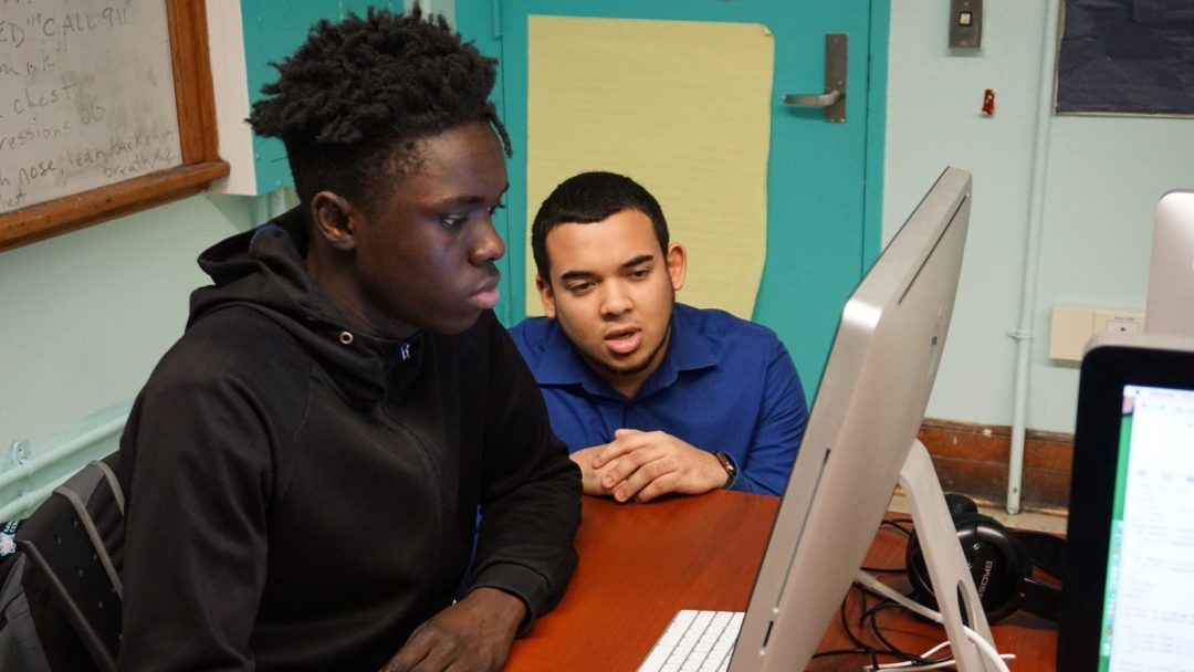 CTE Apprentice, Kyle Pierre, kneeling next to CTE student at computer terminal