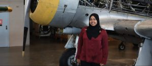 Sadia Ahmed standing next to front of a WWII-era fighter plane