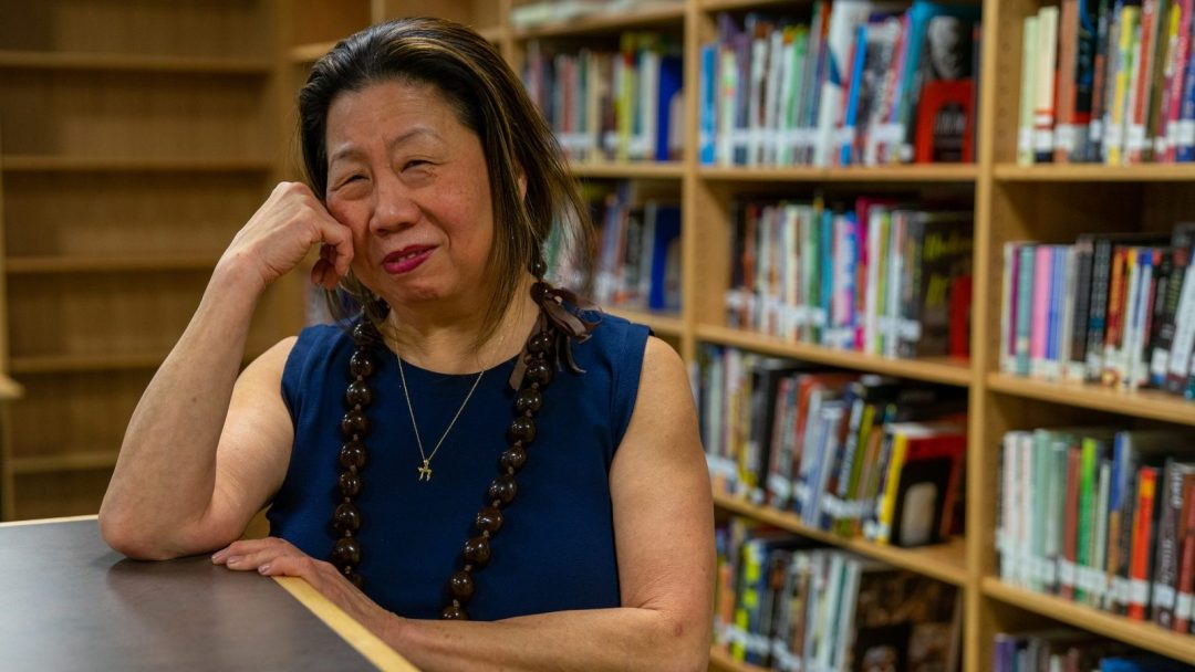 Carol Sun leaning over a bookshelf inside a school library