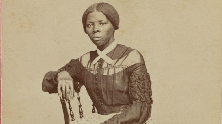 Harriet Tubman, sitting in chair and looking at viewer