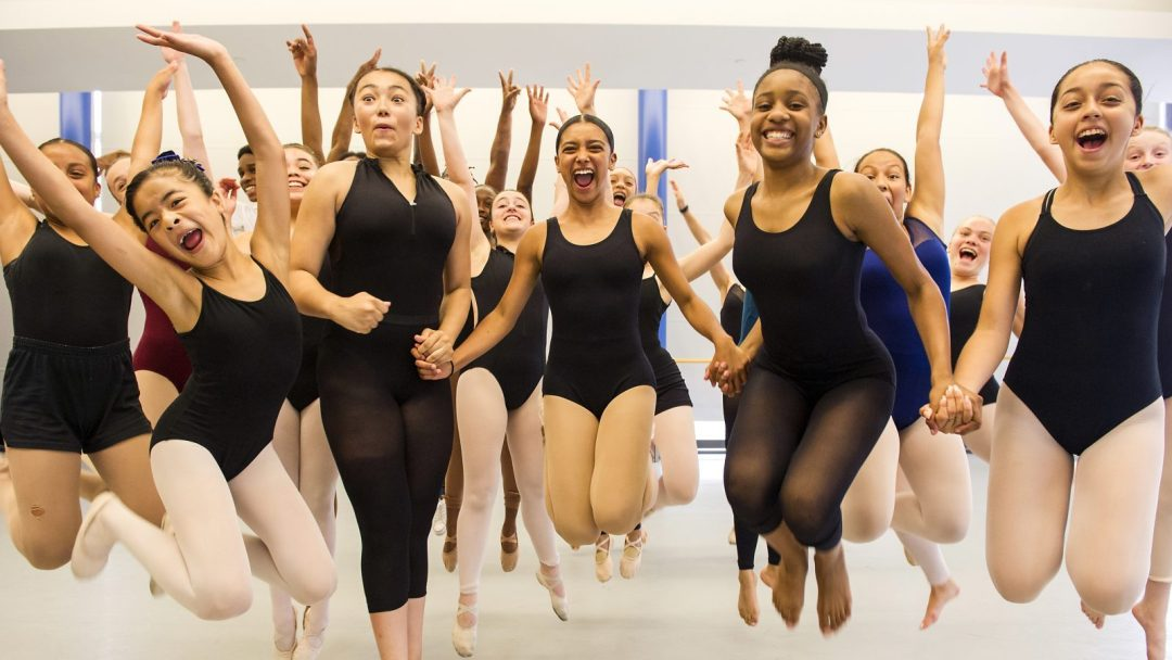 Students from Dance Class Jumping into the Air While Hand-in-Hand