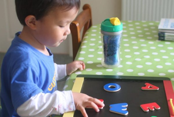 A child working on a letterboard at their kitchen table