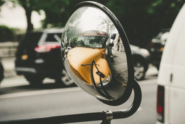 Close-up of a driver-side mirror on a school bus