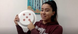 Teacher Damaris Rosado-James counting five dots on a paper plate