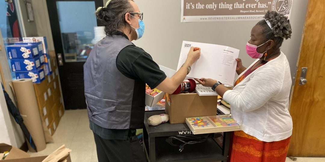 REC Site Supervisor Brett Schneider (left) checking off supplies with fellow teacher