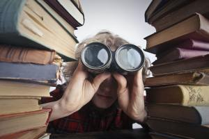 Person holding a pair of binoculars in between two stacks of books