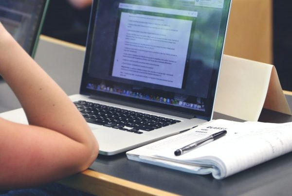 Side close-up of a person working on laptop