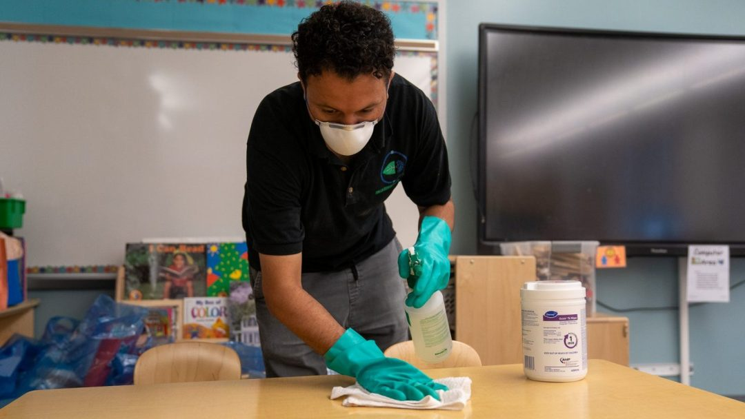 Custodian cleaning a school desk with disinfectant wipes