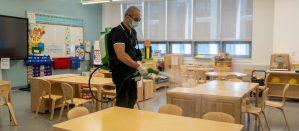 School custodian spraying a disinfectant inside a classroom