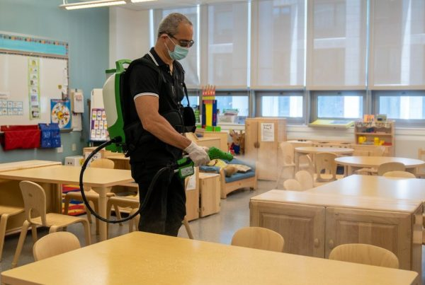 School custodian spraying a disinfectant inside a classroom