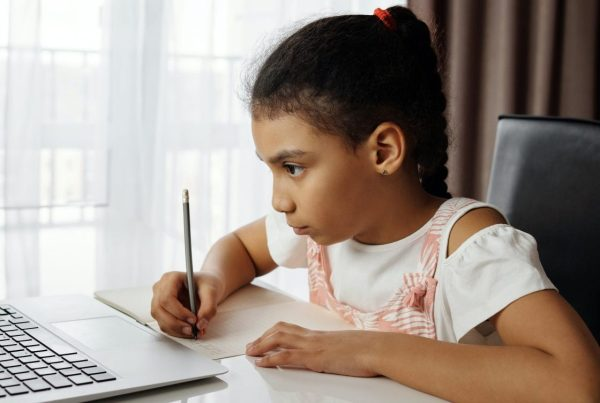 Girl sitting down in front of her laptop, pen in hand taking notes