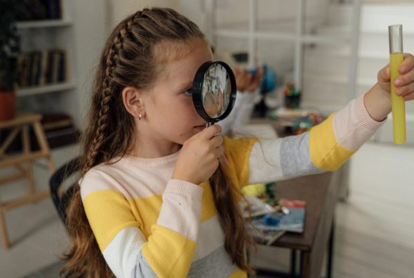 Girl holding a magnifying glass to her face while observing a glass vial filled with a yellow substance