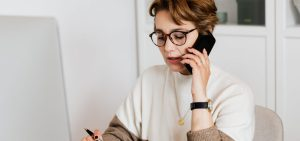 Woman speaking with someone over the phone with pen ready in hand to take notes
