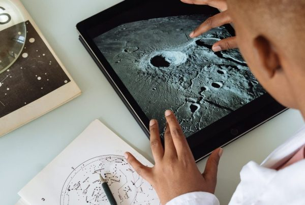 Rear view of student checking out the surface of the Moon on a tablet while referencing a map in an old lunar textbook