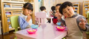 Three students sitting at a table eating snacks during an early education class