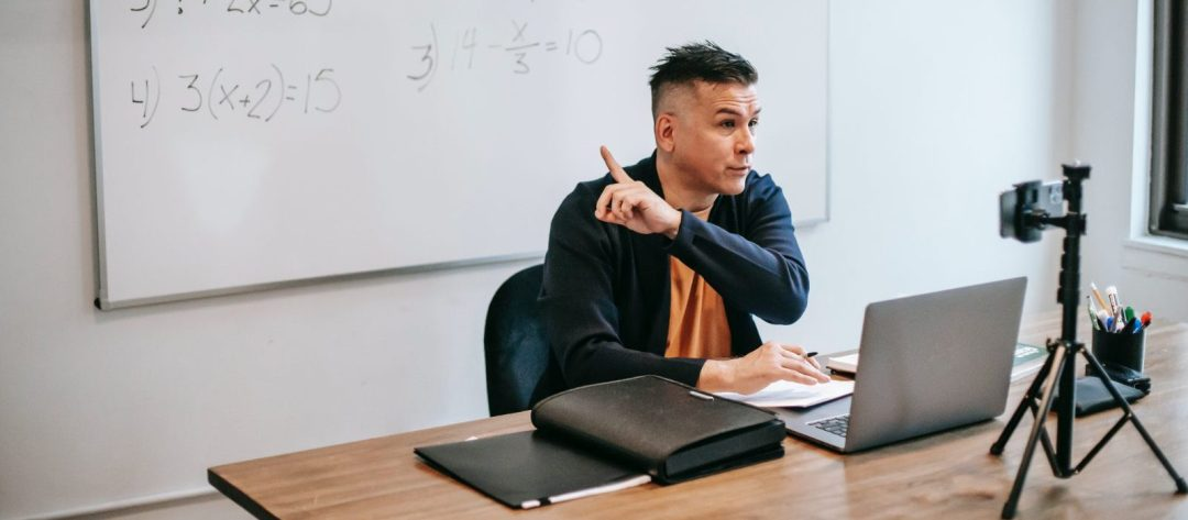 Teacher pointing to a whiteboard behind him while remote teaching on a laptop