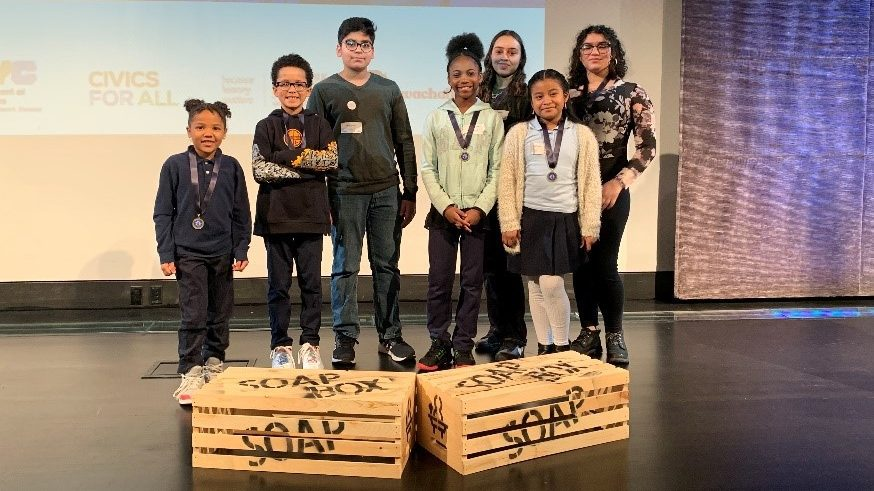 Students standing on a stage behind their 'soap boxes'